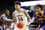 Cincinnati's Jarron Cumberland (34) drives against East Carolina's Brandon Suggs (4) during the second half of an NCAA college basketball game, Sunday, Jan. 19, 2020, in Cincinnati. (AP Photo/John Minchillo)