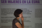 A woman attends the inauguration of an exhibit that recounts harrowing stories of dictatorship-era gender-based violence, at the former Naval Mechanics School, ESMA, once the era's biggest clandestine detention and torture center, now the Buenos Aires ESMA museum and memorial, in Buenos Aires, Argentina, Thursday, March 14, 2019. The sign above reads in Spanish