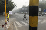 A policewoman wears a pollution mask and and hold a banner saying obey odd and even, remove pollution, in New Delhi, India, Monday, Nov. 4, 2019. Authorities in New Delhi are restricting the use of private vehicles on the roads under an