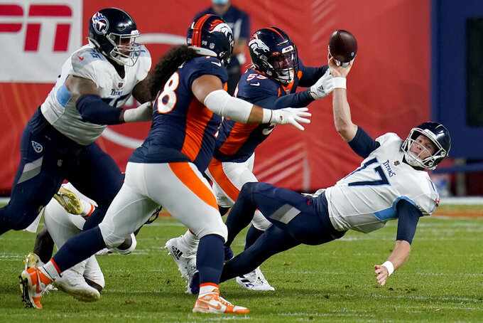 Tennessee Titans quarterback Ryan Tannehill, right, get the pass off as he is pressured by Denver Broncos outside linebacker Bradley Chubb, rear, and nose tackle Mike Purcell (98) during the first half of an NFL football game, Monday, Sept. 14, 2020, in Denver. (AP Photo/Jack Dempsey)