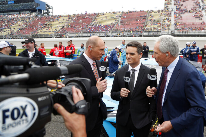 FILE - In this June 9, 2019, file photo, Fox Sports broadcasters Adam Alexander, left, Jeff Gordon, center, and Darrell Waltrip are shown on pit row before the NASCAR cup series auto race at Michigan International Speedway in Brooklyn, Mich. NASCAR will have a much different feel when it resumes this weekend as the two-man broadcast team for Fox will not travel to Darlington Raceway and instead call the race from a studio in Charlotte.(AP Photo/Carlos Osorio, FIle)