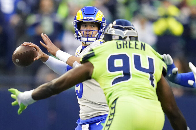 Los Angeles Rams quarterback Matthew Stafford, left, passes under pressure from Seattle Seahawks defensive end Rasheem Green (94) during the first half of an NFL football game, Thursday, Oct. 7, 2021, in Seattle. (AP Photo/Elaine Thompson)