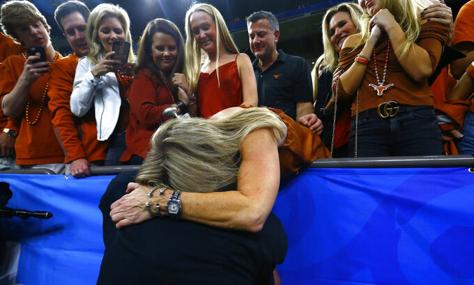 Texas quarterback Sam Ehlinger hugs his mother, Jena Ehlinger, after Texas defeated Georgia 28-21 in the Sugar Bowl NCAA college football game in New Orleans, Tuesday, Jan. 1, 2019. (AP Photo/Butch Dill)