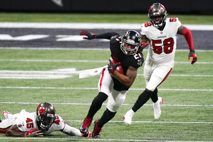 Atlanta Falcons running back Todd Gurley (21) runs past Tampa Bay Buccaneers outside linebacker Shaquil Barrett (58) during the first half of an NFL football game, Sunday, Dec. 20, 2020, in Atlanta. (AP Photo/Brynn Anderson)