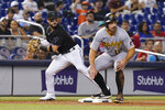 Pittsburgh Pirates' Bryan Reynolds, right, stands at third after advancing on a double by Anthony Alford during the third inning of a baseball game, Saturday, Sept. 18, 2021, in Miami. Miami Marlins shortstop Eddy Alvarez is at left. (AP Photo/Marta Lavandier)