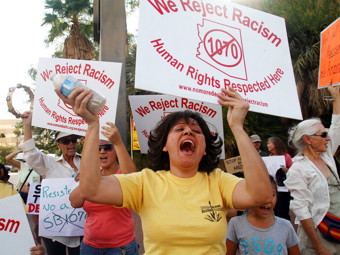 """FILE - In this Monday, June 25, 2012, file photo, a small crowd protests at the Arizona State Building in Tucson, Ariz., during a rally after the U.S. Supreme Court's decision on Arizona SB1070. On Tuesday, Nov. 5, 2019, residents voted not to designate Tucson a """"sanctuary city"""" with further restrictions on how and when police officers can enforce immigration laws. The initiative explicitly aimed to neuter the 2010 Arizona immigration law known as SB1070, which drew mass protests and a boycott of the state. Courts threw out much of the law but upheld the requirement for officers to check immigration papers when they suspect someone is in the country illegally. (David Sanders/Arizona Daily Star via AP, File)"""