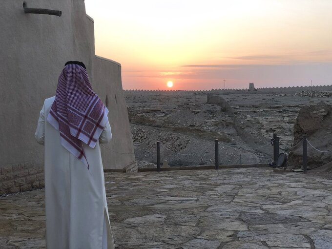 A man watches the sun setting over Dhiriyah, a UNESCO World Heritage site that includes a 17th-century fortress, mosques and clay-colored structures just outside of Saudi Arabia's capital of Riyadh on Sunday, Dec. 16, 2018. (AP Photo/Karin Laub)