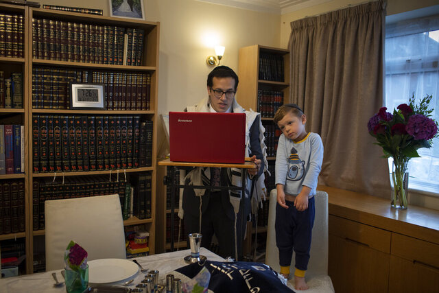 As his 3-year-old son Tzvi looks on, Rabbi Mordechai Chalk leads a service for his congregation via a teleconference app from his home in London on Friday, June 19, 2020, just before sunset. Taking services online-only has been particularly challenging for the Orthodox Jewish community, members of which are proscribed from using electronics on Shabbat, their day of rest. (AP Photo/Elizabeth Dalziel)