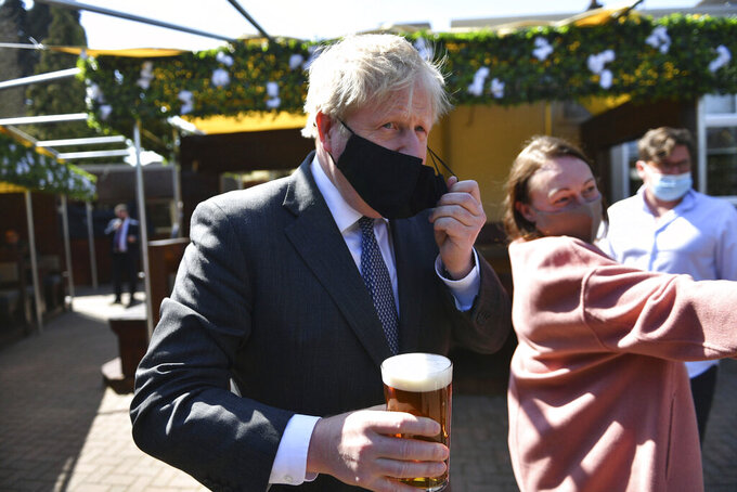 Britain's Prime Minister Boris Johnson removes his mask in the beer garden during a visit to The Mount pub and restaurant in Wolverhampton, central England, Monday April 19, 2021, during the Conservative party election campaign. (Jacob King/Pool via AP)