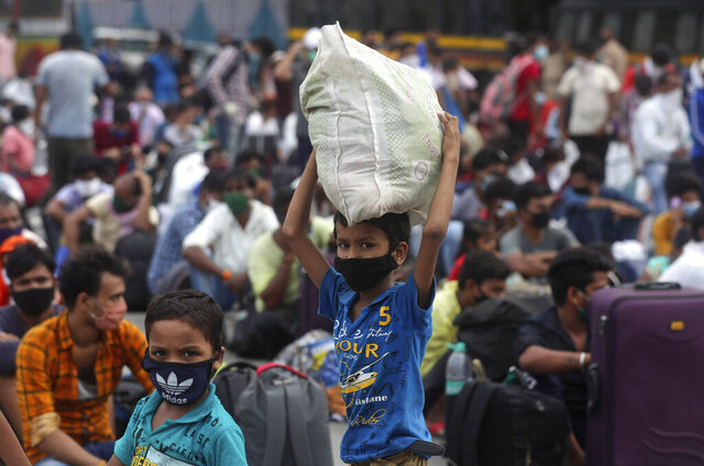 Children of migrant workers from other states wait outside a railway station to catch a train to return to their hometowns, in Mumbai, India, Friday, May 15, 2020. The pandemic has exposed India's deep economic divide as millions of migrant workers have left Indian cities with luggage bags perched on their heads and children in their arms, walking down highways in desperate attempts to reach the countryside. (AP Photo/Rafiq Maqbool)