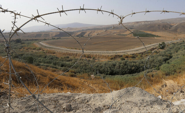 FILE - In this Nov. 13, 2019, file photo, a portion of the Israeli-Jordanian border ​​is viewed through a barbed wire fence from Baqoura, in the Jordan Valley. Jordan's Foreign Ministry on Thursday, April 30, 2020 announced that Israeli farmers will no longer be allowed to work their fields in an enclave of southern Jordan, ending a more than 25-year arrangement meant to shore up a historic peace agreement. (AP Photo/Raad Adayleh, File)