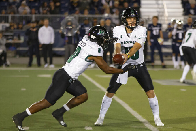 Hawaii quarterback Brayden Schager (13) hands the ball off to Dae Dae Hunter (0) during the first half against Nevada in an NCAA college football game in Reno, Nev., Saturday, Oct. 16, 2021. (AP Photo/Tom R. Smedes)