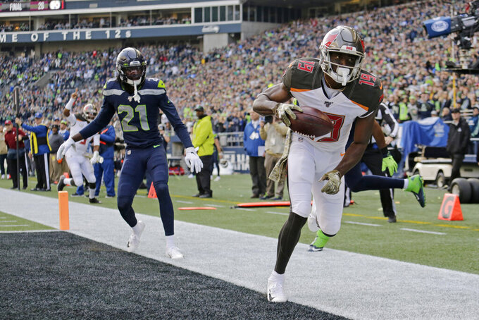 Tampa Bay Buccaneers wide receiver Breshad Perriman, right, scores a touchdown ahead of Seattle Seahawks cornerback Tre Flowers (21) during the first half of an NFL football game, Sunday, Nov. 3, 2019, in Seattle. (AP Photo/John Froschauer)