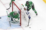 Dallas Stars goaltender Anton Khudobin (35) looks back for the puck as Tampa Bay Lightning center Blake Coleman (20) and Stars left wing Joel Kiviranta (25) work behind the net during the second period of Game 3 of the NHL hockey Stanley Cup Final, Wednesday, Sept. 23, 2020, in Edmonton, Alberta. (Jason Franson/The Canadian Press via AP)