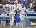 Chicago Cubs' Addison Russell, right greets Kris Bryant after Bryant scored against the Los Angeles Dodgers during the first inning of a baseball game in Los Angeles, Thursday, June 13, 2019. (AP Photo/Kyusung Gong)