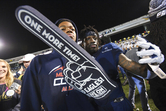 Georgia Southern quarterback Shai Werts poses with a fan after an NCAA college football game against Appalachian State, Thursday, Oct. 25, 2018, in Statesboro, Ga. Georgia Southern won 34-14. (AP Photo/John Amis)