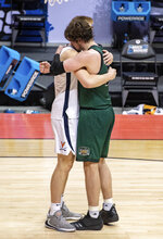 Virginia forward Sam Hauser (10), left, and Ohio forward Ben Vander Plas, right, meet on the court after Ohio's win over Virginia in a first-round game in the NCAA men's college basketball tournament, Saturday, March 20, 2021, at Assembly Hall in Bloomington, Ind. (AP Photo/Doug McSchooler)
