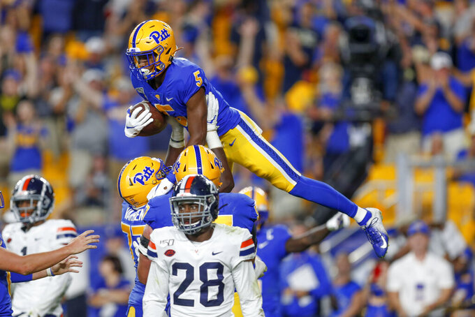 Pittsburgh wide receiver Tre Tipton (5) is lifted  by offensive lineman Carter Warren (77) after he made a touchdown catch against Virginia in the second quarter of an NCAA college football game, Saturday, Aug. 31, 2019, in Pittsburgh. Virginia safety Brenton Nelson (28) walks away at bottom. (AP Photo/Keith Srakocic)