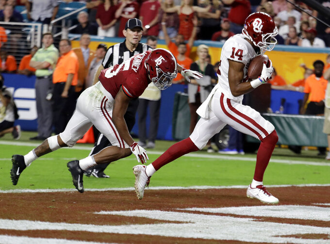 Oklahoma wide receiver Charleston Rambo (14) catches a pass for in the end zone for a touchdown ahead of Alabama defensive back Xavier McKinney (15), during the second half of the Orange Bowl NCAA college football game, Saturday, Dec. 29, 2018, in Miami Gardens, Fla. (AP Photo/Lynne Sladky)