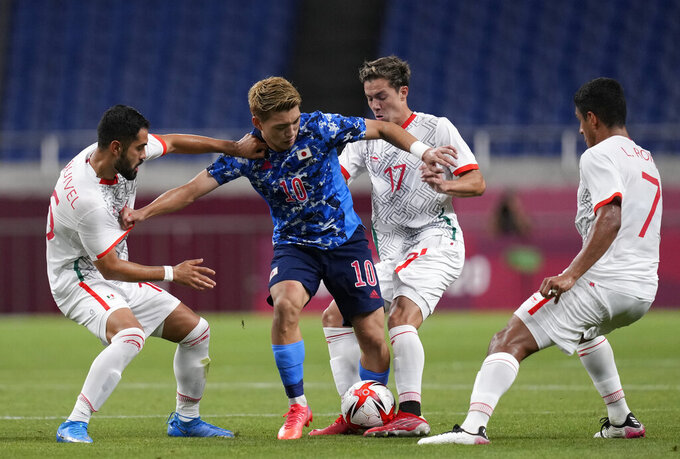 Japan's Ritsu Doan is challenged by Mexican players during a men's soccer match at the 2020 Summer Olympics, Sunday, July 25, 2021, in Saitama, Japan. (AP Photo/Martin Mejia)