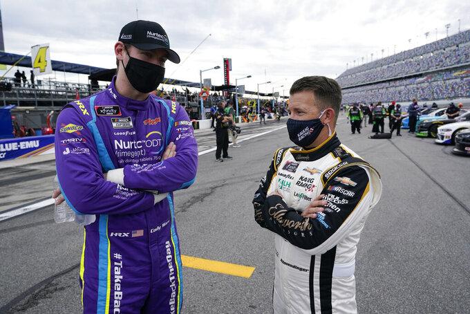 Cody Ware, left, and A J Allmendinger talk on pit road before the NASCAR Xfinity Series auto race at Daytona International Speedway, Saturday, Feb. 13, 2021, in Daytona Beach, Fla. (AP Photo/John Raoux)