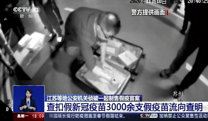 In this image taken from video footage run by China's CCTV via AP Video, policemen seize fake COVID-19 vaccines in Kunshan in eastern China's Jiangsu Province, Nov. 18, 2020. Chinese police have arrested more than 80 suspected members of a criminal group that was manufacturing and selling fake COVID-19 vaccines, including to other countries. (CCTV via AP Video)