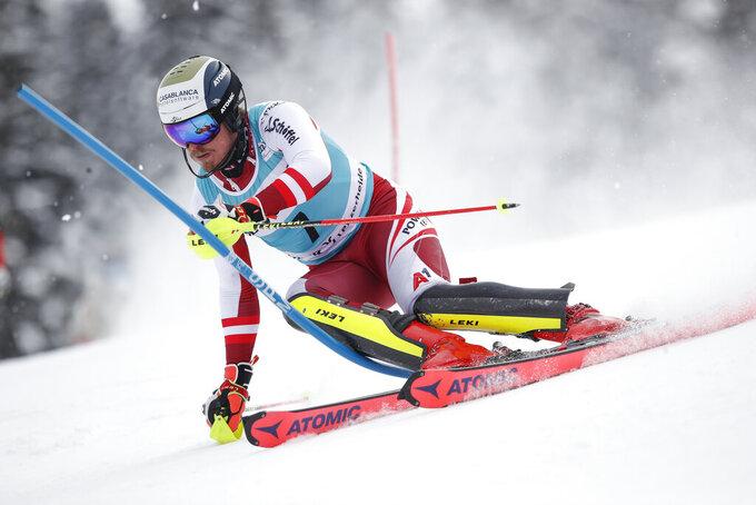Austria's Manuel Feller speeds down the course during an alpine ski, men's World Cup slalom, in Lenzerheide, Switzerland, Sunday, March 21, 2021. (AP Photo/Gabriele Facciotti)