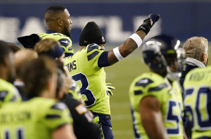 Seattle Seahawks strong safety Jamal Adams raises his fist during the national anthem beore an NFL football game against the Arizona Cardinals, Thursday, Nov. 19, 2020, in Seattle. (AP Photo/Elaine Thompson)