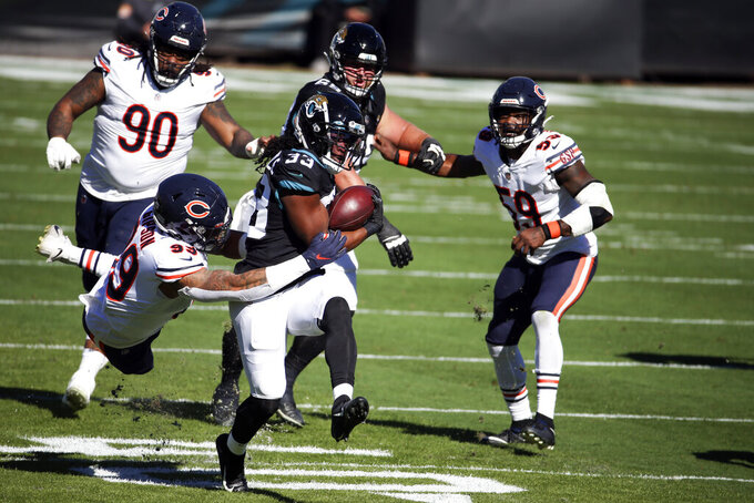 Jacksonville Jaguars running back Dare Ogunbowale (33) gains yardage as he gets past the Chicago Bears defense including linebacker Trevis Gipson (99) and nose tackle John Jenkins (90) during the first half of an NFL football game, Sunday, Dec. 27, 2020, in Jacksonville, Fla. (AP Photo/Stephen B. Morton)