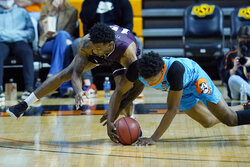 Texas Southern forward Justin Hopkins, left, and Oklahoma State's Matthew-Alexander Moncrieffe, right, dive for a loose ball during the first half of an NCAA college basketball game in Stillwater, Okla., Saturday, Nov. 28, 2020. (AP Photo/Sue Ogrocki)