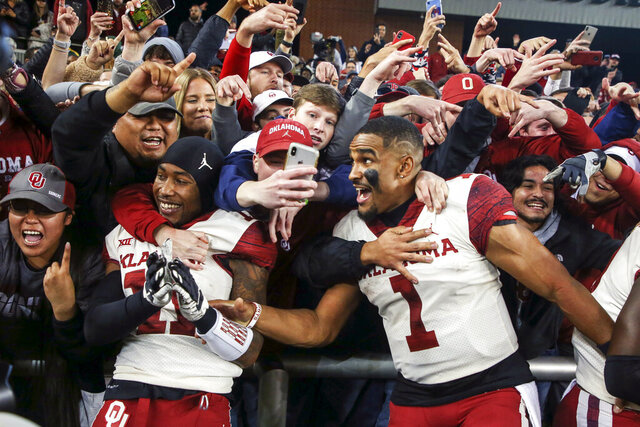 Oklahoma cornerback Parnell Motley (11) and quarterback Jalen Hurts (1) celebrate with fans after their 34-31 win over Baylor in an NCAA college football game, Saturday, Nov. 16, 2019, in Waco, Texas. (Ian Maule/Tulsa World via AP)