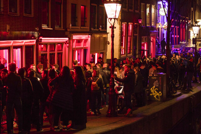 -FILE- In this Friday March 29, 2019, file image tourists bathing in a red glow emanating from the windows and peep shows' neon lights are packed shoulder to shoulder as they shuffle through the alleys in Amsterdam's red light district, Netherlands. The capital is banning tours that take groups past the city's famed