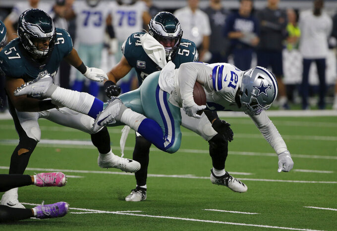 Dallas Cowboys running back Ezekiel Elliott (21) fights through the line of scrimmage for a gain of short yardage as Philadelphia Eagles' T.J. Edwards (57) and Kamu Grugier-Hill (54) attempt the stop in the second half of an NFL football game in Arlington, Texas, Sunday, Oct. 20, 2019. (AP Photo/Michael Ainsworth)