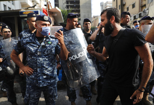 An anti-government protester shouts at riot police, near the scene where a Lebanese man killed himself on Beirut's commercial Hamra Street, apparently because of the deteriorating economic and financial crisis in the country, in Beirut, Lebanon, Friday, July 3, 2020. The man left a note that reads in Arabic: