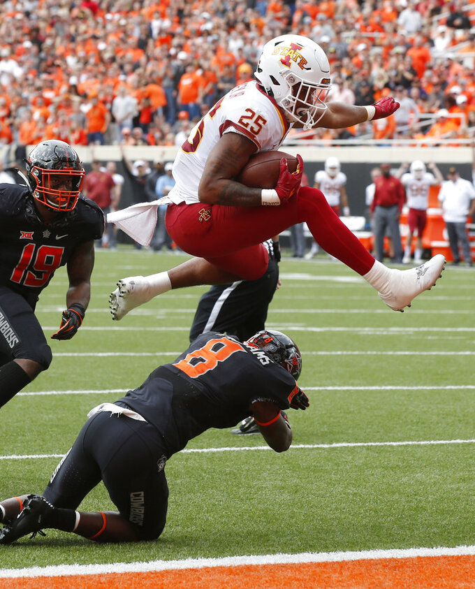 Iowa State running back Sheldon Croney Jr. (25) leaps over Oklahoma State cornerback Rodarius Williams (8) into the endzone for a touchdown in the first half of an NCAA college football game in Stillwater, Okla., Saturday, Oct. 6, 2018. Oklahoma State's Justin Phillips (19) is at left. (AP Photo/Sue Ogrocki)