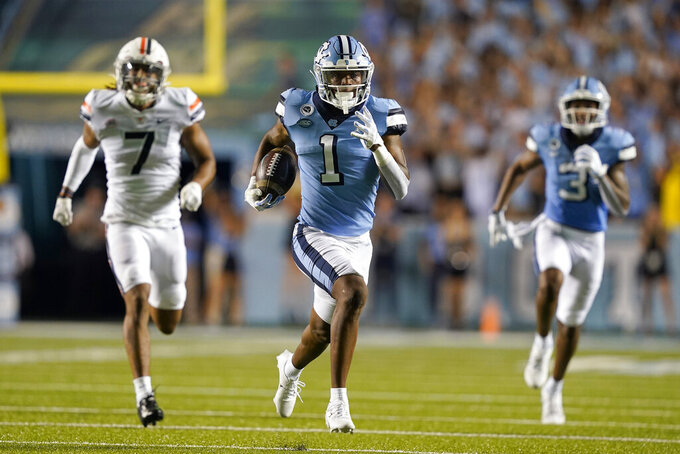 North Carolina wide receiver Khafre Brown (1) runs for a touchdown as Virginia outside linebacker Noah Taylor (7) chases during the first half of an NCAA college football game in Chapel Hill, N.C., Saturday, Sept. 18, 2021. Brown scored on the play. (AP Photo/Gerry Broome)