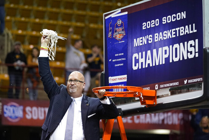 East Tennessee State head coach Steve Forbes waves the net in the air after cutting it from the rim to celebrate his team's over Wofford for the NCAA men's college basketball championship for the Southern Conference tournament, Monday, March 9, 2020, in Asheville, N.C. (AP Photo/Kathy Kmonicek)