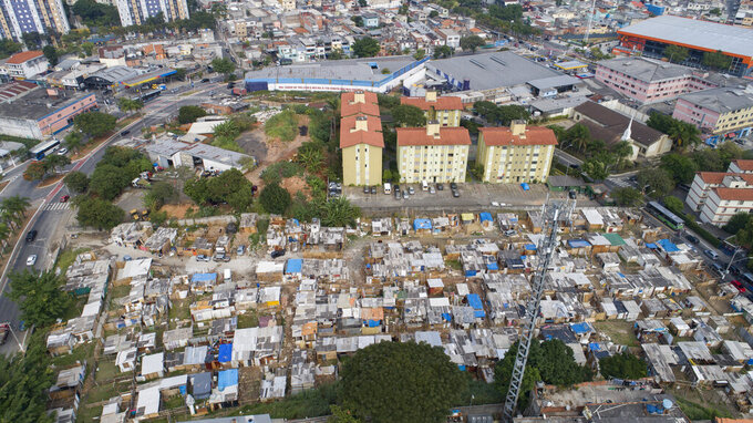 FILE - This May 15, 2021 file photo shows an aerial view of the Penha Brasil favela where families have started relocating during the coronavirus pandemic in Sao Paulo, Brazil. The pandemic shantytown sprang up virtually overnight when people began using scavenged wooden boards to build shacks on a plot of empty land in Sao Paulo, Brazil's biggest city. (AP Photo/Andre Penner, File)