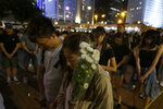 Attendees take part in a vigil to mourn the death of a woman in Hong Kong Saturday, July 6, 2019. The vigil is being held for the woman who fell to her death this week, one of three apparent suicides linked to ongoing protests over fears that freedoms are being eroded in this semi-autonomous Chinese territory. (AP Photo/Andy Wong)