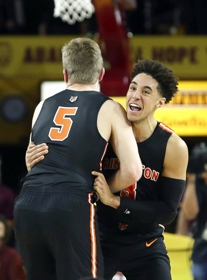 File- This Dec. 29, 2018, file photo shows Princeton guard Devin Cannady, right, and teammate Drew Friberg (5) celebrating following a victory over Arizona State in an NCAA college basketball game, in Tempe, Ariz.  Cannady has been suspended from the Princeton University basketball team after throwing a punch at a campus police officer and being arrested following a confrontation at a convenience store. (AP Photo/Ralph Freso, File)