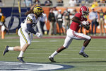 Alabama wide receiver Jerry Jeudy (4) runs after a reception past Michigan linebacker Jordan Glasgow (29) during the first half of the Citrus Bowl NCAA college football game, Wednesday, Jan. 1, 2020, in Orlando, Fla. (AP Photo/John Raoux)
