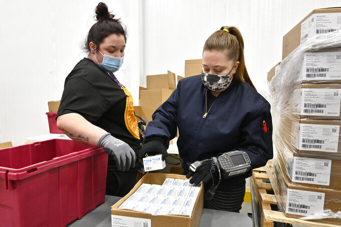 Employees with the McKesson Corporation scan a box of the Johnson &  Johnson COVID-19 vaccine while filling an order at their shipping facility in Shepherdsville, Ky., Monday, March 1, 2021. (AP Photo/Timothy D. Easley, Pool)