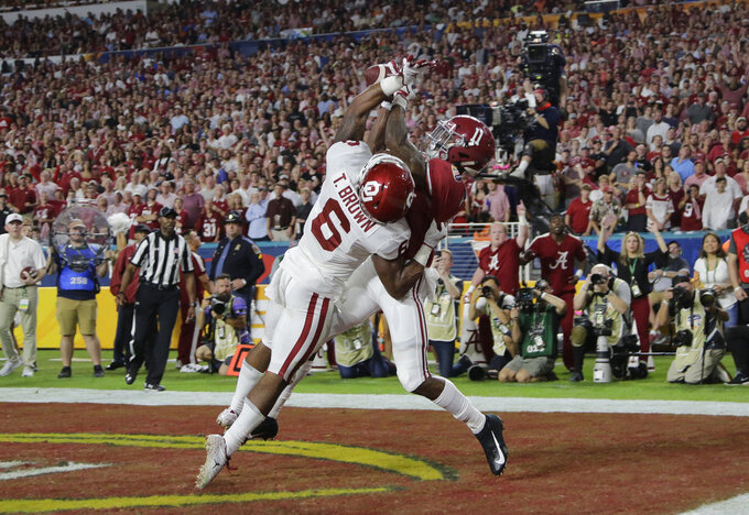 Alabama wide receiver Henry Ruggs III (11) catches a pass in the end zone for touchdown as Oklahoma cornerback Tre Brown (6) defends, during the first half of the Orange Bowl NCAA college football game, Saturday, Dec. 29, 2018, in Miami Gardens, Fla. (AP Photo/Lynne Sladky)