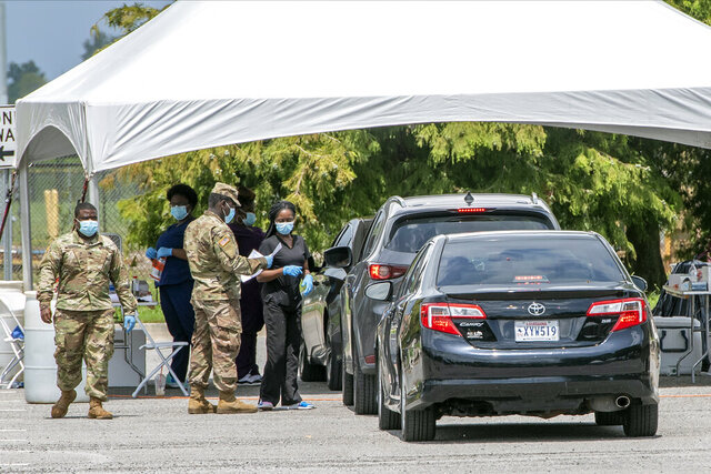 People line up at the Covid-19 testing site at LSU's Alex Box Stadium parking lot, Tuesday, July 7, 2020, in Baton Rouge, La. (Bill Feig/The Advocate via AP)