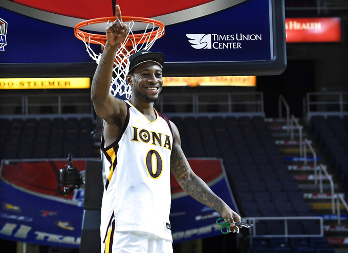 FILE- In this March 11, 2019, file photo Iona guard and tournament MVP Rickey McGill celebrates cutting the net after a win against Monmouth in the championship NCAA college basketball game during the Metro Atlantic Athletic Conference tournament in Albany, N.Y. (AP Photo/Hans Pennink, File)