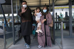 Families evacuated from Kabul, Afghanistan, walk through the terminal before boarding a bus after they arrived at Washington Dulles International Airport, in Chantilly, Va., on Monday, Aug. 30, 2021. (AP Photo/Jose Luis Magana)