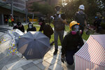 A protestor carrying molotov cocktails stands with others holding umbrellas as they wait for a possible volley of tear gas at the Hong Kong Polytechnic University campus in Hong Kong, Thursday, Nov. 14, 2019. University students from mainland China and Taiwan are fleeing Hong Kong, while those from three Scandinavian countries have been moved or urged to leave as college campuses become the latest battleground in the city's 5-month-long anti-government unrest. (AP Photo/Ng Han Guan)