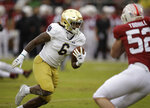 Notre Dame's Tony Jones Jr., left, runs for a touchdown against Stanford's Casey Toohill (52) in the first half of an NCAA college football game Saturday, Nov. 30, 2019, in Stanford, Calif. (AP Photo/Ben Margot)