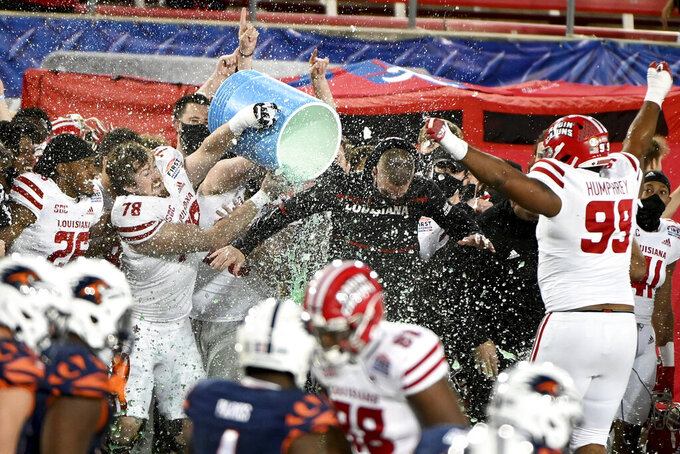 Louisiana-Lafayette coach Billy Napier is doused by offensive lineman Luke Junkunc (78) during the fourth quarter of the team's 31-24 win over UTSA in the First Responder Bowl NCAA college football game in Dallas, Saturday, Dec. 26, 2020. (AP Photo/Matt Strasen)