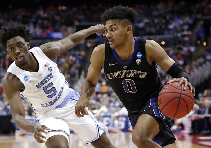Washington's Jamal Bey (0) drives past North Carolina's Nassir Little (5) in the second half during a second round men's college basketball game in the NCAA Tournament in Columbus, Ohio, Sunday, March 24, 2019. North Carolina won 81-59. (AP Photo/Tony Dejak)